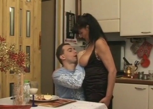 Mommy lets her bored-looking son suck on her tits